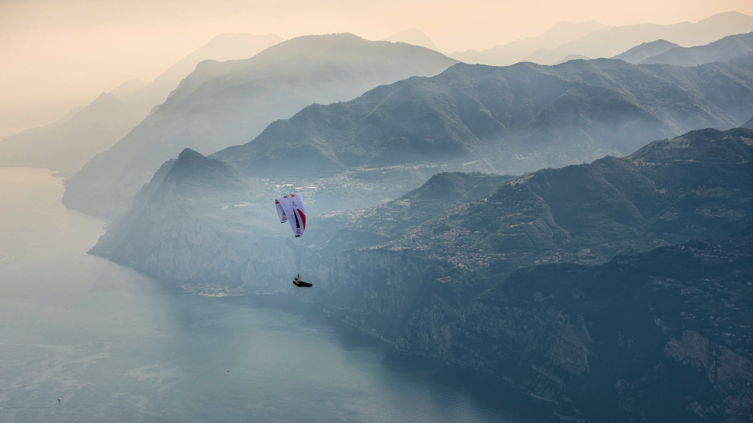 epa06073926 A handout photo made available by Global Newsroom on 07 July 2017 of Christian Maurer (SUI1) flying during the Red Bull X-Alps above Lake Garda, Italy, 06 July 2017. At this extreme adventure race 31 pilots out of 20 nations have to fly from Salzburg/ Austria to Monaco passing turnpoints in Slovenia, Germany, Italy, Switzerland and France with a paraglider. The only alternative to manage the 2.500 kilometer distance is to hike.  EPA/SEBASTIAN MARKO  HANDOUT EDITORIAL USE ONLY/NO SALES
