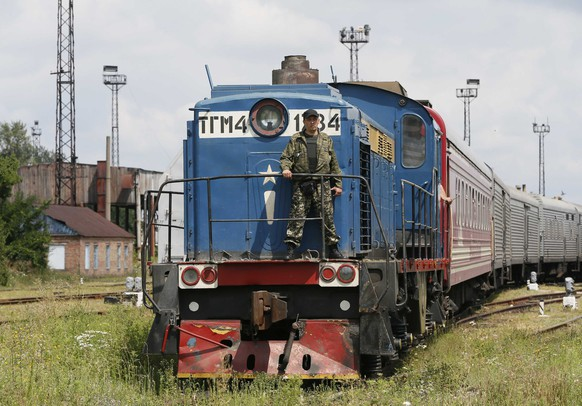 A guard stands on a train carrying the remains of victims of Malaysia Airlines MH17 downed over rebel-held territory in eastern Ukraine after it arrived in the city of Kharkiv, eastern Ukraine July 22, 2014. Almost 300 people were killed when the Malaysian airliner went down on July 17. REUTERS/Gleb Garanich (UKRAINE - Tags: POLITICS DISASTER TRANSPORT CIVIL UNREST)