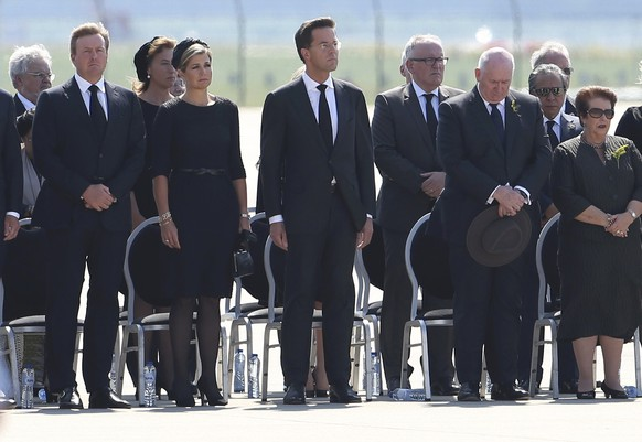 King Willem Alexander (L) and Queen Maxima of the Netherlands (2ndL), Dutch Prime Minister Mark Rutte (C) and officials attend a national reception ceremony at Eindhoven airport July 23, 2014 for the remains of the victims of Malaysia Airlines MH17 downed over rebel-held territory in eastern Ukraine. Two aircraft carrying the remains of some of the 298 passengers who died on flight MH17 touched down at an airport in the Dutch city of Eindhoven on Wednesday, as next-of-kin and Dutch and foreign officials looked on. The remains of the victims of the downing of the flight over eastern Ukraine, 193 of whom were Dutch, will be brought over the next few days to a military base in Hilversum, the Netherlands. The Netherlands declared Wednesday the country's first day of mourning in more than half a century.      REUTERS/Francois Lenoir (NETHERLANDS  - Tags: TRANSPORT POLITICS DISASTER CIVIL UNREST ROYALS)