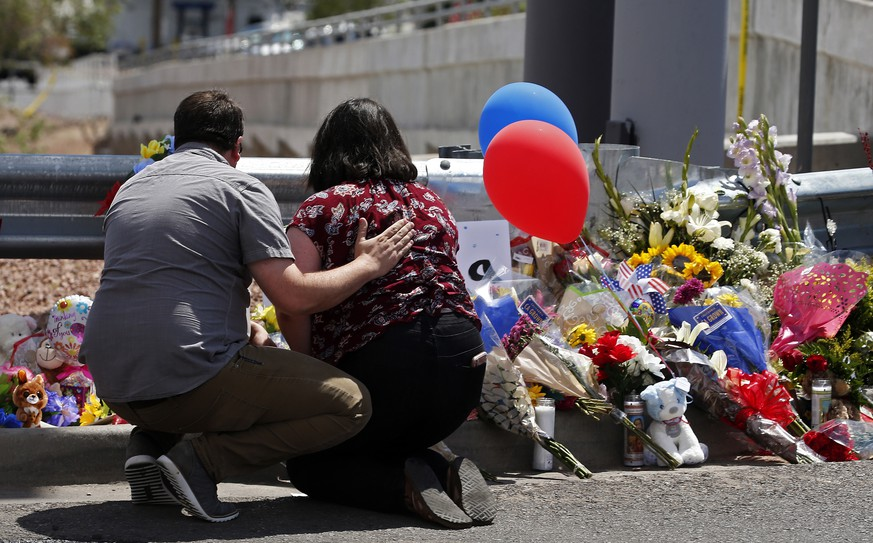 epa07757081 A man comforts a woman while kneeling in front of a make shift memorial along the street behind the scene of a mass shooting at a Walmart in El Paso, Texas, 04 August 2019. A day earlier, 20 people killed and 26 injured in a mass shooting at the Walmart in El Paso, Texa Prosecutors said that they will seek the death penalty against Patrick Crusiuss, a 21-year-old man, accused of the mass shooting.  EPA/LARRY W. SMITH
