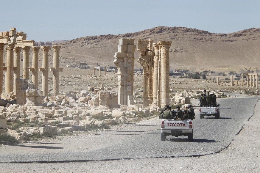 FILE PHOTO: Syrian army soldiers drive past the Arch of Triumph in the historic city of Palmyra, in Homs Governorate, Syria April 1, 2016. REUTERS/Omar Sanadiki/File Photo
