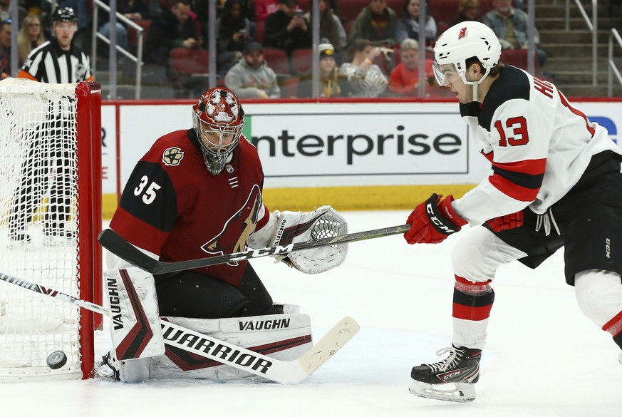 Arizona Coyotes goaltender Darcy Kuemper (35) makes a save on a shot by New Jersey Devils center Nico Hischier (13) during the first period of an NHL hockey game Friday, Jan. 4, 2019, in Glendale, Ariz. (AP Photo/Ross D. Franklin)