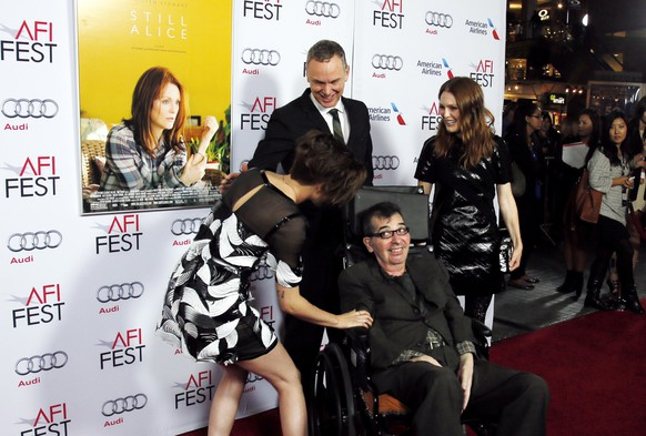 Actress Kristen Stewart (L) greets director Richard Glatzer as director Wash Westmoreland (top, C) and actress Julianne Moore (R) look on at a special screening of the film
