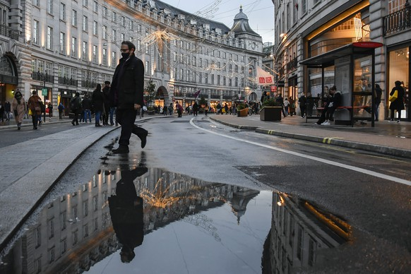 A man wears a face mask while he walks and is reflected into a puddle in Regent Street, ahead of the new Tier-4 restriction measures, in London, Saturday, Dec. 19, 2020. Britain's Prime Minister Boris Johnson says Christmas gatherings cannot go ahead and non-essential shops must close in London and much of southern England as he imposed a new, higher level of coronavirus restrictions to curb rapidly spreading infections.(AP Photo/Alberto Pezzali)