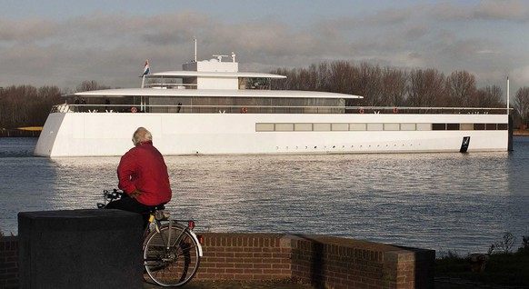 epa03487506 A man on a bicycle watches the yacht of late Apple co-founder Steve Jobs, the 'Venus', made by Dutch shipbuilder Royal de Vries in Aalsmeer, departing for a trial run at the Noordzeekanaal near Velsen, The Netherlands, 26 November 2012 - more than a year after the death of the visionary entrepreneur. The yacht was designed by Philippe Starck and sports clean lines and mostly uninterrupted surfaces.  EPA/OLAF KRAAK