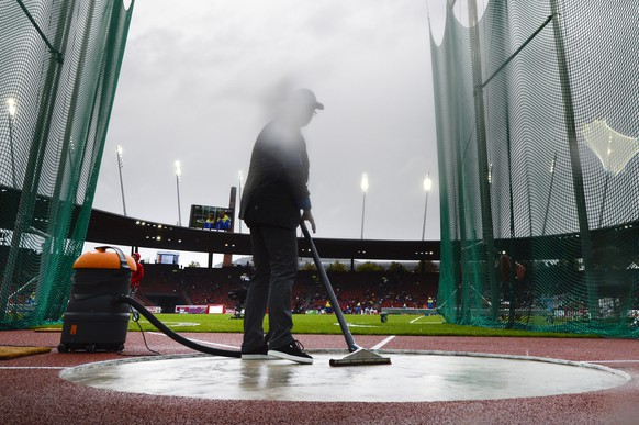 A worker cleans the discus circle from rain, during the women's discus throw qualifying event, at the fourth day of the European Athletics Championships in the Letzigrund Stadium in Zurich, Switzerland, Friday, August 15, 2014. (KEYSTONE/Jean-Christophe Bott)