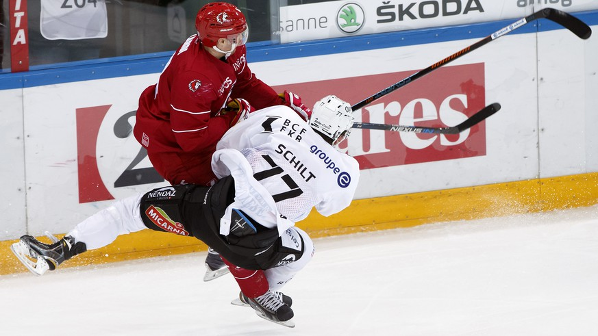 Lausanne's Federico Lardi, left, body checks Fribourg's Sebastian Schilt, right, during a National League A regular season game of the Swiss Championship between Lausanne HC and HC Fribourg Gotteron, at the Malley stadium in Lausanne, Saturday, January 9, 2015. (KEYSTONE/Salvatore Di Nolfi)