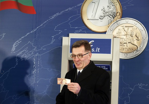 Lithuania's Prime Minister Algirdas Butkevicius, looks at the 10 Euro banknote which he withdrew from an ATM cash machine in Vilnius, Lithuania, early Thursday, Jan. 1, 2015. The Baltic state of Lithuania early Thursday became the 19th European Union member to adopt the joint European currency, the euro. (AP Photo/Mindaugas Kulbis)