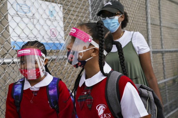FILE - In this Sept. 9, 2020, file photo, students wear protective masks as they arrive for classes at the Immaculate Conception School while observing COVID-19 prevention protocols in The Bronx borough of New York. New York City has again delayed the planned start of in-person learning for most of the more than 1 million students in its public school system.  Mayor Bill de Blasio announced Thursday, Sept. 17,  that most elementary school students would do remote-only learning until Sept. 29. Middle and high schools would stay remote through Oct. 1.(AP Photo/John Minchillo)