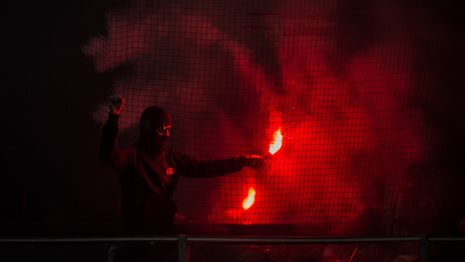 A fan of Lausanne with a flare during the preliminary round game of the National League between HC Ambri-Piotta and Lausanne HC, at the ice stadium Valascia in Ambri, on Sunday, January 14, 2018. (KEYSTONE/Ti-Press/Pablo Gianinazzi)