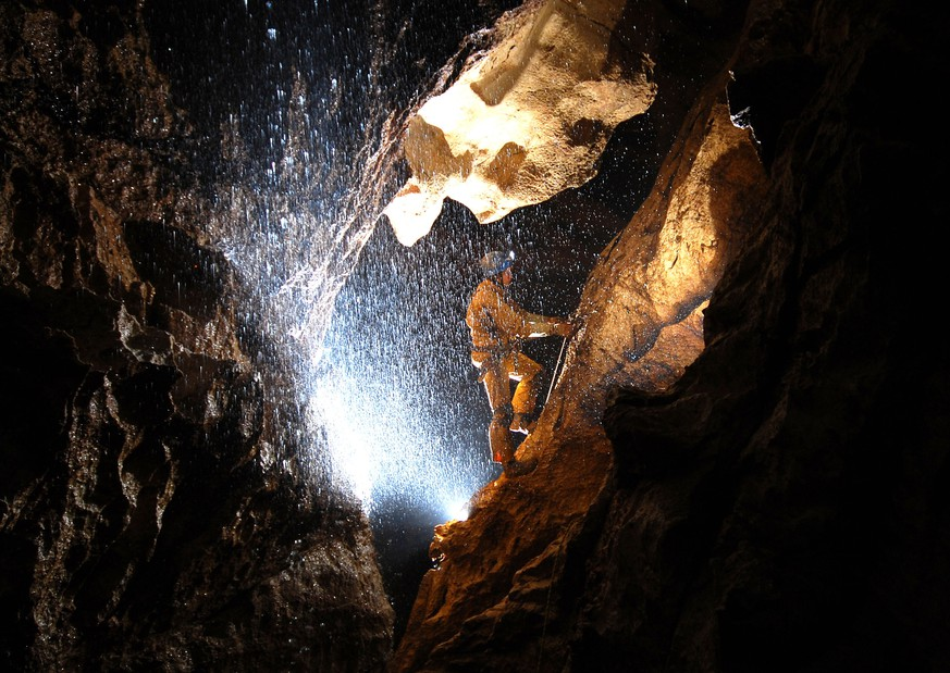 MARKTSCHELLENBERG, GERMANY - JUNE 11:  In this undated handout photo a spelunker explores the Riesending cave where an explorer is currently lying injured 1,000 meters below since June 8, 2014 near Marktschellenberg, Germany. The man, along with two colleagues, was exploring the Riesending vertical cave, which is over 20km long and up to 1,148 meters deep, when he was struck by rocks and severely injured. Since then specialist rescue workers from Switzerland and Italy have arrived to help with the arduous rescue effort, which could take up to several more days and even weeks.   (Photo by Bergwacht Bayern via Getty Images)