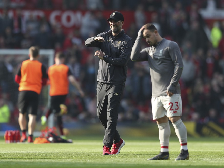 Liverpool manager Juergen Klopp smiles next to Liverpool's Xherdan Shaqiri prior to the English Premier League soccer match between Manchester United and Liverpool at Old Trafford stadium in Manchester, England, Sunday, Feb. 24, 2019. (AP Photo/Jon Super)