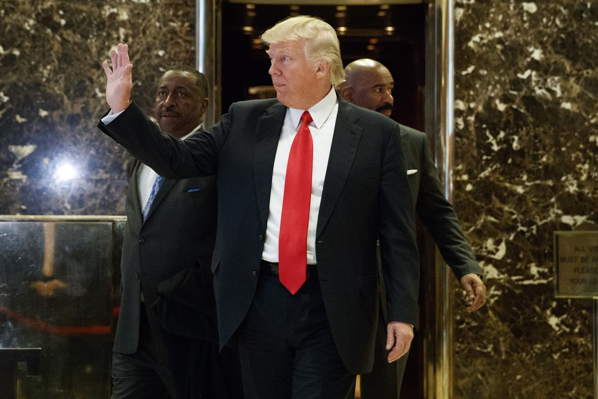 President-elect Donald Trump waves as he walks out of the elevator in the lobby of Trump Tower in New York, Friday, Jan. 13, 2017. (AP Photo/Evan Vucci)