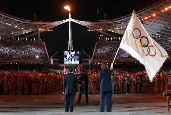 Athens mayor Dora Bakoyiannis, right, prepares to hand the Olympic Flag to Beijing mayor Wang Qishan, during the closing ceremony for the 2004 Olympic Games at the Olympic stadium in Athens, Greece, Sunday, Aug. 29, 2004. (AP Photo/Elaine Thompson)