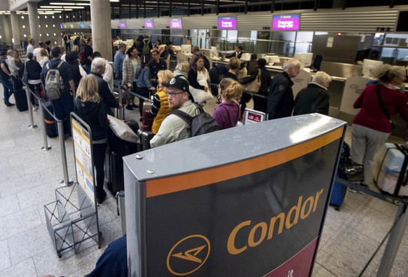 People queue at a counter of Condor airline, owned by Thomas Cook, at the airport in Frankfurt, Germany, Monday, Sept. 23, 2019. Germany's Condor airline says it can no longer carry travelers who booked with Thomas Cook companies. British tour company Thomas Cook collapsed early Monday after failing to secure emergency funding, leaving tens of thousands of vacationers stranded abroad. (AP Photo/Michael Probst)