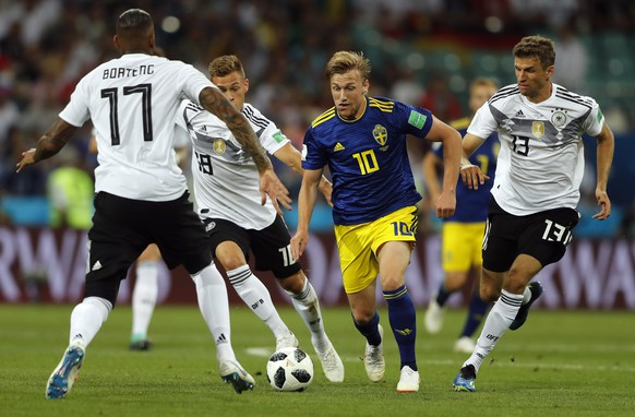Sweden's Emil Forsberg, second from right, is tackled by Germany's Marco Reus, left, Joshua Kimmich, second from left, and Thomas Mueller during the group F match between Germany and Sweden at the 2018 soccer World Cup in the Fisht Stadium in Sochi, Russia, Saturday, June 23, 2018. (AP Photo/Frank Augstein)
