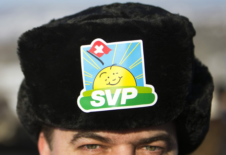 Thomas Fuchs, member of the Swiss People's Party (SVP) wears a hat with the party emblem at a party meeting in Coinsins near Nyon, December 4, 2010. The meeting is held as a landsgemeinde, a 700-year tradition of an open-air assembly in which citizens can take key political decisions directly by raising their hands, after the University of Lausanne (UNIL) refused to host the meeting. REUTERS/Valentin Flauraud (SWITZERLAND - Tags: POLITICS) - RTXVDQO
