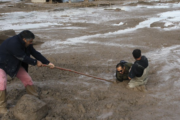 Two men try to help another cross a mud flat in Copiapo, Chile, Thursday, March 26, 2015. Unusually heavy thunder storms and torrential rains that began on Tuesday have blocked roads, caused power outages and affected some 600 people on this normally dry region. (AP Photo/Aton Chile, Marcelo Hernandez) CHILE OUT - NO USAR EN CHILE