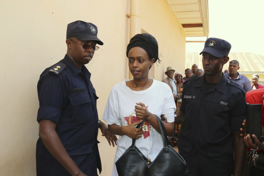 FILE - In this Friday, Oct. 6, 2017 file photo, former Rwanda presidential candidate Diane Rwigara is escorted by policemen to a court where she denied charges of insurrection and forgery that she says are linked to her criticism of the government's human rights record. The former Rwandan presidential challenger was freed on bail Friday, Oct. 5, 2018 after more than a year behind bars. (AP Photo, File)