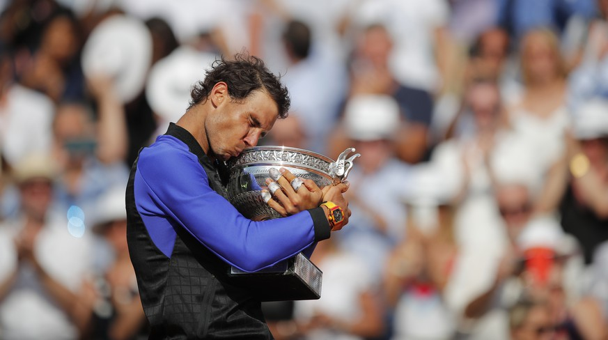 Spain's Rafael Nadal kisses the trophy as he celebrates winning his tenth French Open title against Switzerland's Stan Wawrinka in three sets, 6-2, 6-3, 6-1, during their men's final match of the French Open tennis tournament at the Roland Garros stadium, in Paris, France, Sunday, June 11, 2017. (AP Photo/Christophe Ena)