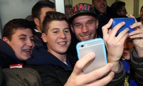 epa04545120 German forward Lukas Podolski (R) arrives at Milan's Airport of Linate in Milan, Italy, 02 January 2015. Inter Milan have agreed final details on signing Arsenal's Lukas Podolski on loan for the rest of the season, Gazzetta dello Sport and other Italian media reported 02 January 2015.  EPA/MATTEO BAZZI