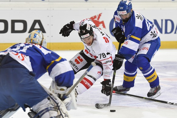 Davos' Gilles Senn, left, and Daniel Rahimi, right, fight for the puck with Team Canada's Marc-Antoine Pouliot, center, during the game between HC Davos and Team Canada, at the 90th Spengler Cup ice hockey tournament in Davos, Switzerland, Tuesday, December 27, 2016. (KEYSTONE/Gian Ehrenzeller)