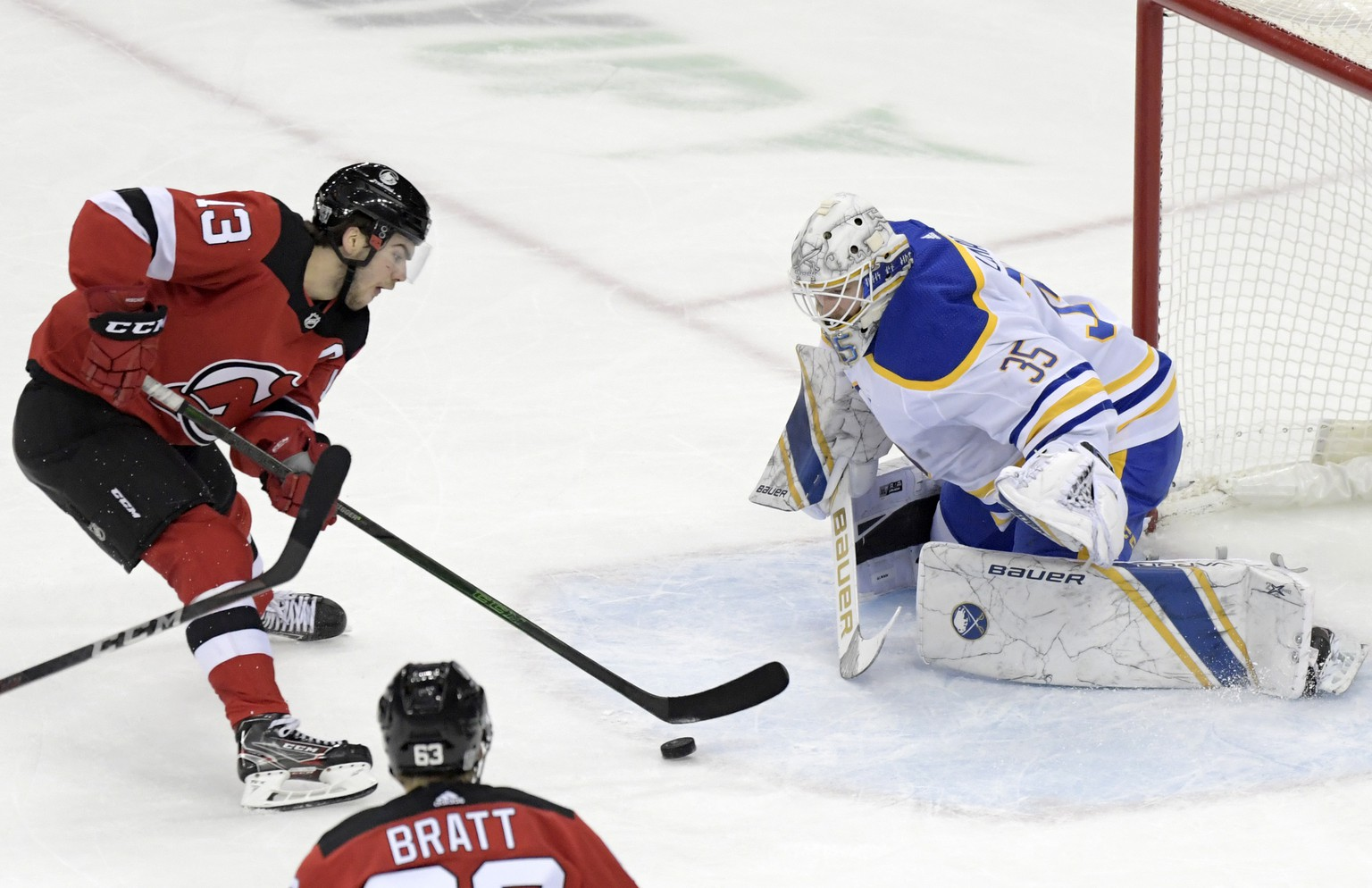 New Jersey Devils center Nico Hischier (13) skates in on Buffalo Sabres goaltender Linus Ullmark (35) during the second period of an NHL hockey game Tuesday, Feb. 23, 2021, in Newark, N.J. (AP Photo/Bill Kostroun)