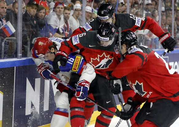 Russia's Sergei Plotnikov, left, challenges for the puck with Canada's, from right, Canada's Nate Mackinnon, Mitch Marner, and Colton Parayko, at the Ice Hockey World Championships semifinal match between Canada and Russia in the LANXESS arena in Cologne, Germany, Saturday, May 20, 2017. (AP Photo/Petr David Josek)
