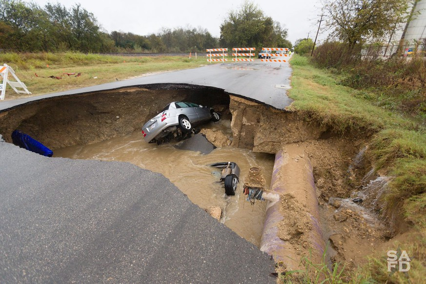 epa05662300 A handout image released 06 December  2016 by the San Antonio Fire Department showing submerged vehicles after reserve deputy Dora Linda (Solis) Nishihara was killed late 04 December when an underground pipe ruptured causing a sinkhole that collapsed a roadway swallowing two vehicles killing Nishihara and injuring a second driver who was rescued in San Antonio, Texas USA, 06 December 2016.  EPA/SAN ANTONIO FIRE DEPARTMENT / HANDOUT  HANDOUT EDITORIAL USE ONLY/NO SALES