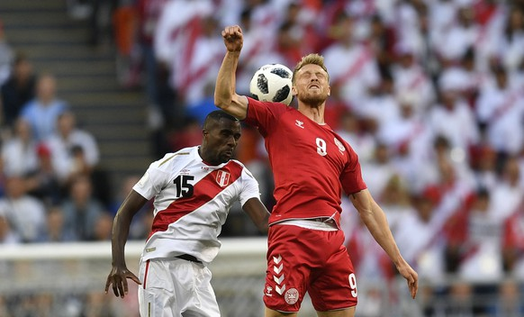 Peru's Christian Ramos, left, heads for the ball with Denmark's Nicolai Jorgensen during the group C match between Peru and Denmark at the 2018 soccer World Cup in the Mordovia Arena in Saransk, Russia, Saturday, June 16, 2018. (AP Photo/Martin Meissner)