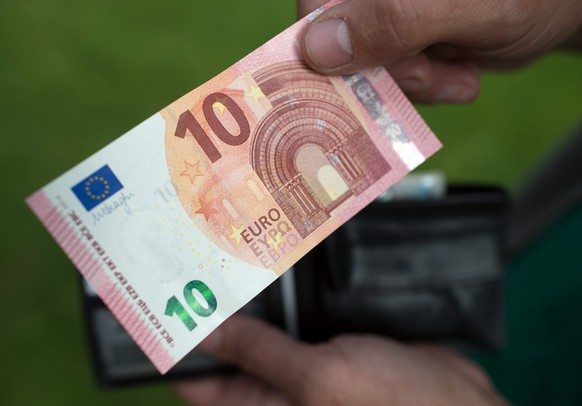 epa04413113 A person holds a 10 euro note in Bonn, Germany, 23 September 2014. The new ten Euro note comes into circulation. The bank note will be harder to forge and is expected to last longer.  EPA/FEDERICO GAMBARINI