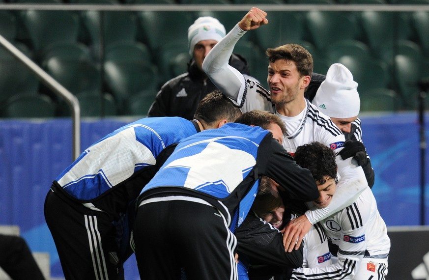 Legia's Thibault Moulin celebrates with his teammates after scoring goal during the Champions League Group F soccer match between Legia Warsaw and Real Madrid, at Stadion Wojska Polskiego, in Warsaw, Poland, Wednesday, Nov. 2, 2016. The match is played at the empty stadium because of earlier fan trouble during a Champions League match against Borussia Dortmund. (AP Photo/Alik Keplicz)