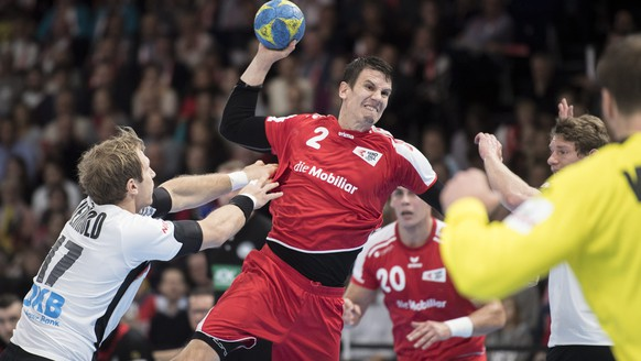 epa05619140 Swiss Andy Schmid, center, in action against Germany's Uwe Gensheimer, right, during the Handball EHF Euro 2018 qualification game between Switzerland and Germany in Zurich, Switzerland, Saturday, November 05, 2016.  EPA/ENNIO LEANZA