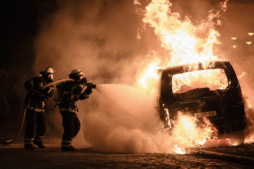 epa06074634 Firefighters extinguish the fire of a burning car during riots at the G20 summit in Hamburg, Germany, 08 July 2017. The G20 Summit (or G-20 or Group of Twenty) is an international forum for governments from 20 major economies. The summit is taking place in Hamburg 07 to 08 July 2017.  EPA/CLEMENS BILAN