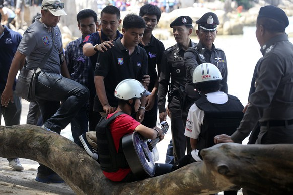 Two workers from Myanmar (wearing helmets and handcuffs), suspected of killing two British tourists on the island of Koh Tao last month, are surrounded by Thai police officers during a re-enactment of the alleged crime, where the bodies of the tourists were found on the island October 3, 2014. The two workers have admitted to killing David Miller and Hannah Witheridge, two British tourists, on the island in southern Thailand, police said on Friday, in a case that has threatened to further damage the Southeast Asian nation's already bruised tourism sector. The bodies of Miller, 24, and Witheridge, 23, were discovered on a beach on the island of Koh Tao, or Turtle Island, on Sept. 15 close to the hotel where they were staying.    REUTERS/Stringer (THAILAND - Tags: POLITICS CRIME LAW) THAILAND OUT. NO COMMERCIAL OR EDITORIAL SALES IN THAILAND