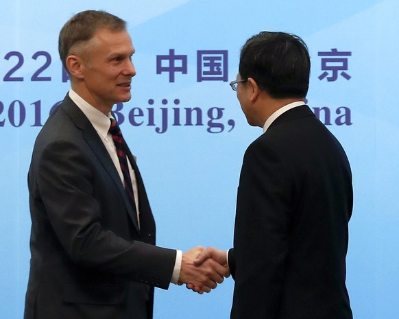 FILE - In this Nov. 21, 2016, file photo, Deputy Chief of Mission of U.S. Embassy Beijing David Rank, left, shakes hands with Director-General of the Department of Treaty and Law of the Foreign Ministry Xu Hong, right, at the opening ceremony of the 14th Plenary Session of the China-US Joint Liaison Group on Law Enforcement Cooperation at the Diaoyutai State Guest House in Beijing. Rank, the top-ranking diplomat at the U.S. Embassy in Beijing has abruptly resigned, telling colleagues he is leaving the foreign service over disagreements with Trump administration policy. (AP Photo/Andy Wong, File)