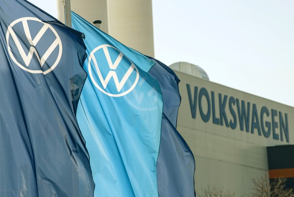 FILE - In this file photo dated Thursday, April 23, 2020, flags wave in front of a factory building during the production restart of the plant of the German manufacturer Volkswagen AG (VW) in Zwickau, Germany. .Carmaker Volkswagen reports Thursday July 30, 2020, an after-tax loss of 1.54 billion euros (dollars 1.81 billion) in the second quarter as the pandemic shut down auto plants and closed dealerships. (AP Photo/Jens Meyer, FILE)