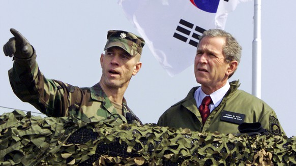FILE - U.S. President George W. Bush, right, looks out at North Korea from Observation Point Ouellette in the Demilitarized Zone, the tense military border between the two Koreas, in Panmunjom, Korea, on Feb. 20, 2002. President Donald Trump is inviting North Korea's Kim Jong Un to shake hands during a visit to the demilitarized zone with South Korea. Trump is scheduled to visit South Korea later Saturday after meetings at the Group of 20 summit in Osaka, Japan. (AP Photo/J. Scott Applewhite, File)George W. Bush
