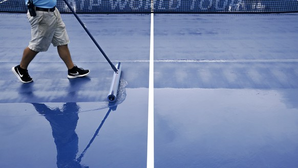 Attendants dry center court before play begins at the Western & Southern Open tennis tournament, Thursday, Aug. 16, 2018, in Mason, Ohio. (AP Photo/John Minchillo)
