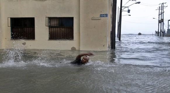 epa06196607 A man swims on a flooded street in Havana, Cuba, 10 September 2017.  Severe storm surge flooding cut power and forced the evacuation of thousands of people in the aftermath of Hurricane Irma.  EPA/Ernesto Mastrascusa