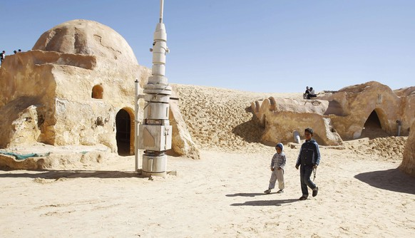 Local boys sell traditional souvenirs in the Star Wars movie set in the Ong Jmal, in the Nefta, south of Tunisia February 22, 2014.  Picture taken February 22, 2014. REUTERS/Zoubeir Souissi (TUNISIA - Tags: SOCIETY TRAVEL)