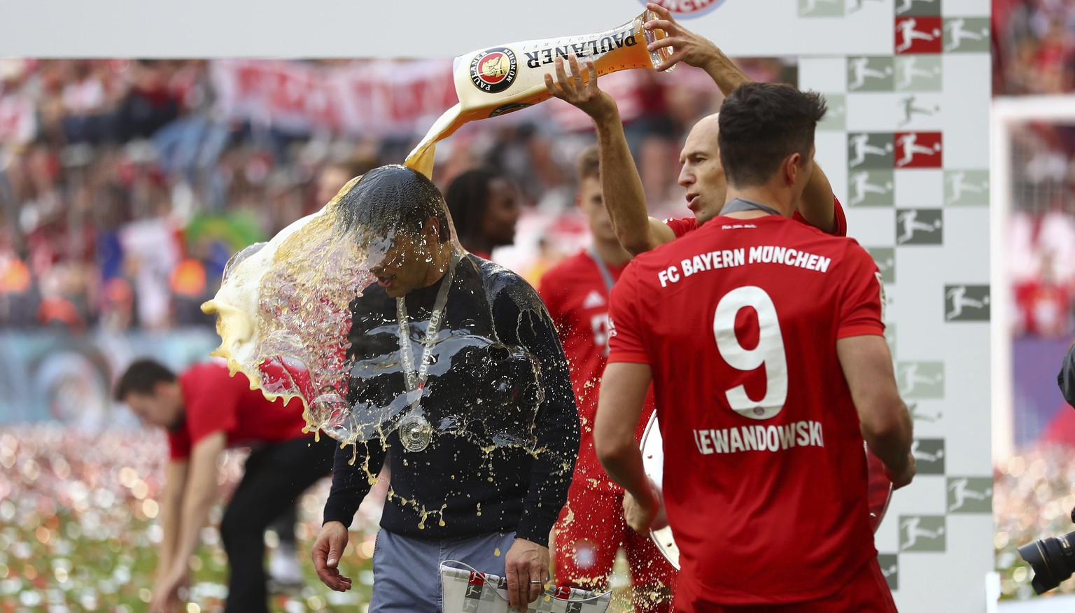 Bayern's Arjen Robben pours beer over coach Niko Kovac to celebrate Bayern's 7th straight Bundesliga title after the German Soccer Bundesliga match between FC Bayern Munich and Eintracht Frankfurt in Munich, Germany, Saturday, May 18, 2019. (AP Photo/Matthias Schrader)