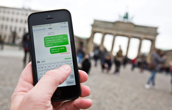 epa04026798 A man uses his iphone to write a text message in front of the Brandenburg Gate in Berlin, Germany, 17 January 2014. According to news reports citing top secret documents, the National Security Agency (NSA) allegedly collects some 200 million text messages and other personal data from mobile phones around the globe every day under an NSA programme codenamed 'Dishfire'.  EPA/MICHAEL KAPPELER