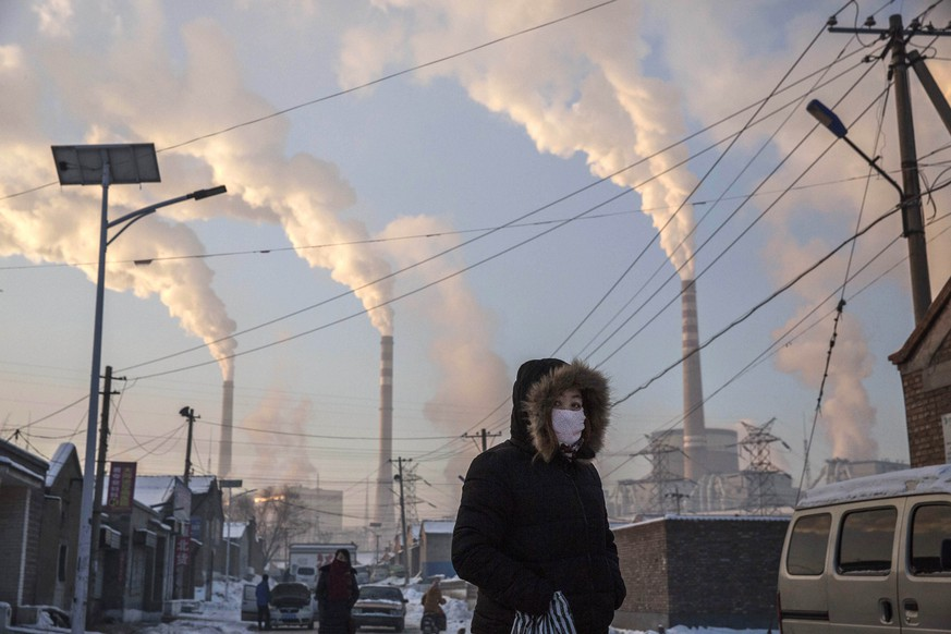 SHANXI, CHINA -NOVEMBER 26: (CHINA, HONG KONG, MACAU, TAIWAN OUT) Smoke billows from stacks as a Chinese woman wears as mask while walking in a neighborhood next to a coal fired power plant on November 26, 2015 in Shanxi, China. A history of heavy dependence on burning coal for energy has made China the source of nearly a third of the world's total carbon dioxide (CO2) emissions, the toxic pollutants widely cited by scientists and environmentalists as the primary cause of global warming. China's government has publicly set 2030 as a deadline to reach the country's emissions peak, and data suggest the country's coal consumption is already in decline. The governments of more than 190 countries are expected to sign an agreement in Paris to set targets on reducing carbon emissions in an attempt to forge a new global agreement on climate change.  (Photo by Kevin Frayer/Getty Images) *** BESTPIX ***