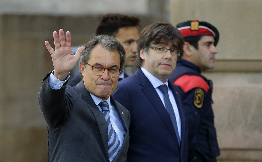 FILE- In this Monday, May 8, 2017 file photo, former Catalan president Artur Mas, left, waves to the crowd next to the then Catalan regional President Carles Puigdemont at the main entrance of the court in Barcelona, Spain. Mas announced Tuesday, Jan. 9, 2018, he is resigning as head of his regional pro-independence party, saying he wants to clear the way for a new generation of leaders pushing for secession from Spain. (AP Photo/Manu Fernandez, File)