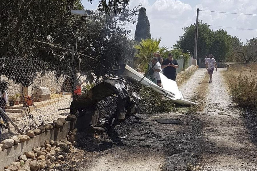 This photo provided by Incendios f.Baleares shows wreckage on a path near Inca in Palma de Mallorca, Spain, Sunday Aug. 25, 2019. Authorities in Mallorca say at least 5 people have died in a collision between a helicopter and a light plane on the Spanish island. (Incendios f.Baleares via AP)