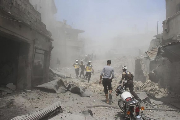 This photo provided by the Syrian Civil Defense group known as the White Helmets, shows Civil Defense workers running in a street that was hit by Syrian government airstrikes, in Jisr al-Shughur, southwest of Idlib, Syria, Thursday, July 11, 2019. In northwestern Syria, where the rebels have their last stronghold and where nearly three million civilians live, government forces have been pushing their way in to at least restore their access to a strategic highway in the area. Despite a Turkey and Russia-backed cease-fire, fighting has raged since late April, displacing hundreds of thousands and killing hundreds. (Syrian Civil Defense White Helmets via AP)