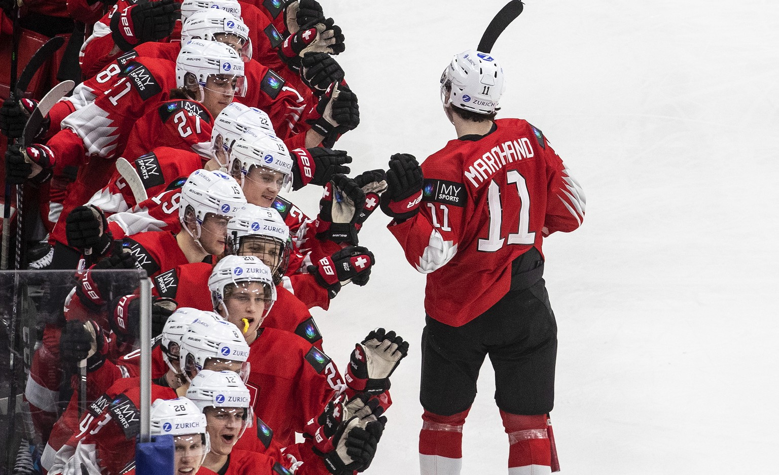 Switzerland's Lionel Marchand (11) celebrates his goal against Austria with teammates during the third period of a game in preparation for the IIHF World Junior Hockey Championships, in Edmonton, Alberta, Tuesday, Dec. 22, 2020. (Jason Franson/The Canadian Press via AP)