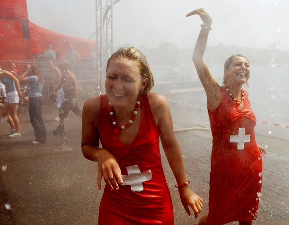 """Dancers are refreshing themselves under a shower, during the 12th Street Parade in Zurich, Switzerland, Saturday, August 9, 2003. Despite temperatures of around 35 degrees hundreds of thousands of fans of techno music joined the event themed """"Let the sun shine"""". (KEYSTONE/Steffen Schmidt)"""