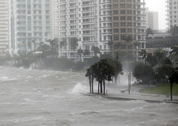 FILE- This Sept. 10, 2017 file photo shows waves crashing over a seawall at the mouth of the Miami River from Biscayne Bay, Fla., as storm surge from Hurricane Irma impacts Miami.  Florida's governor and Legislature promised a dizzying array of fixes following the devastation of last year's hurricanes. But heading into Friday, June 1, 2018,  start of a new storm season, the state has enacted only a few changes. (AP Photo/Wilfredo Lee)